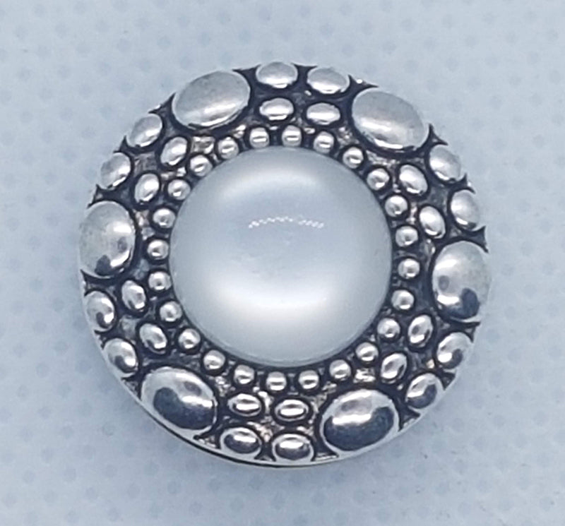 Round snap with silver design and a white stone