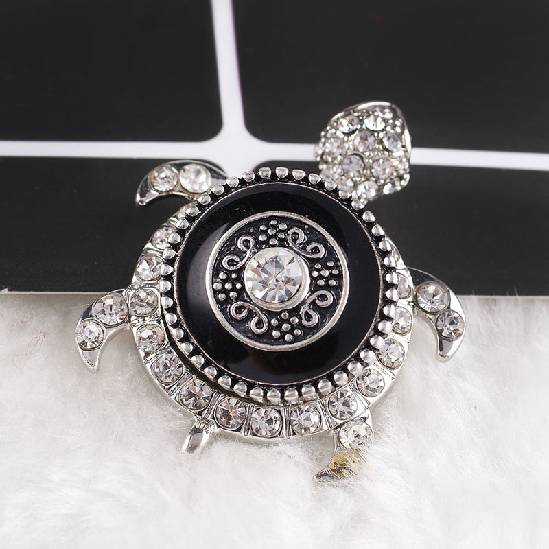 Round snap with a clear rhinestone and black enamel