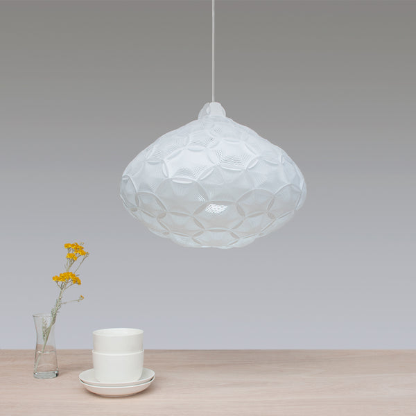 Airy Medium Pendant white lampshade hanging over a wood dining