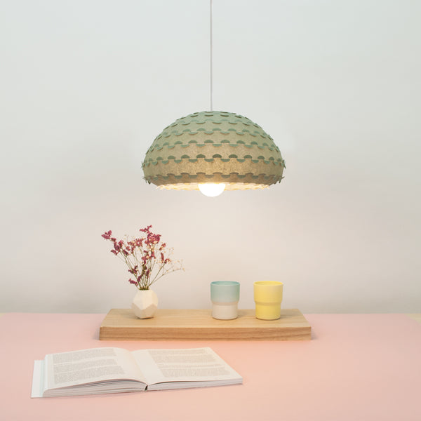 Green pendant lamp shade from washi paper over dining table