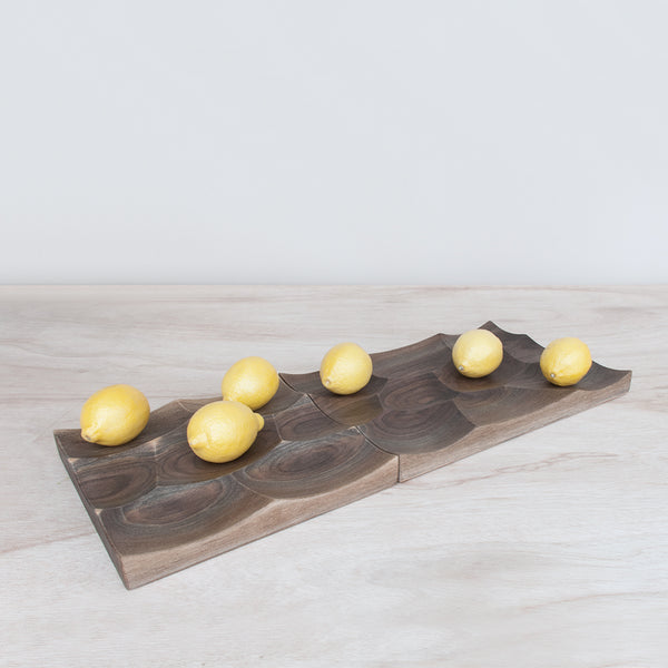 Storm Tray in walnut comes in two sizes large and small and could be tiled infinitely to create a wavy landscape