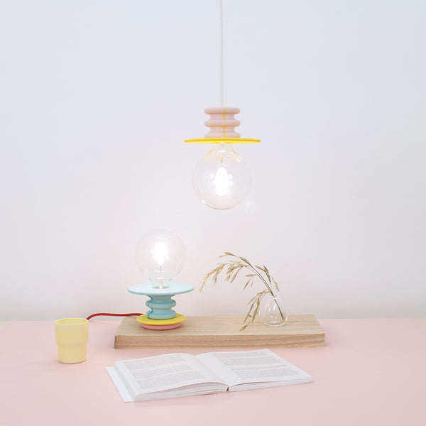 Frutti light is a series of colorful pendant and stand lamps with bright stone bases that celebrate the beauty of a naked bulb.