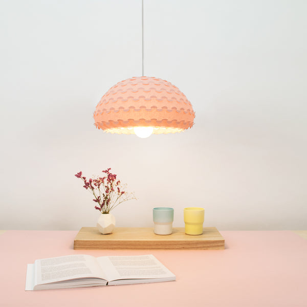 Kasa small hanging lamp in pastel pink color over a dining table interior view