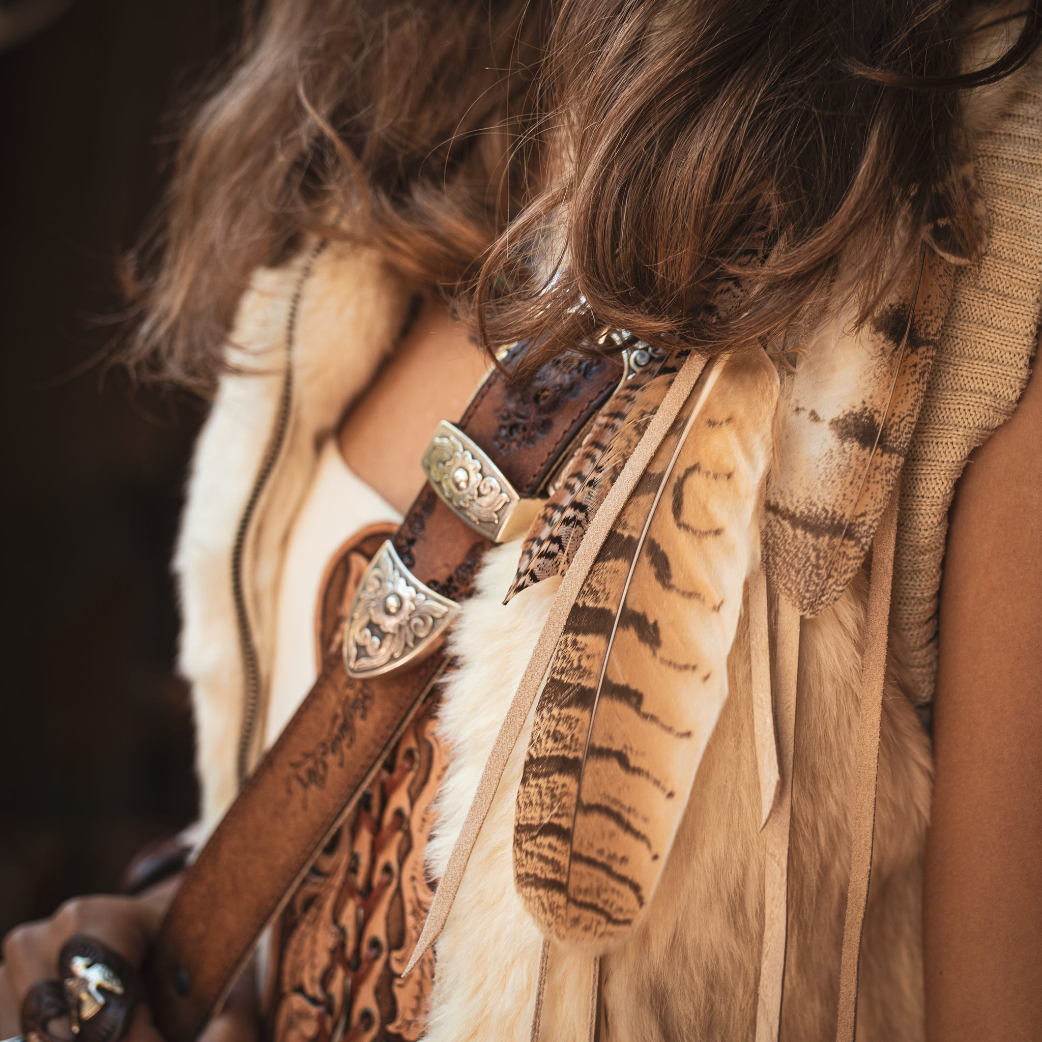 Buffalo girl feather clip & tooled leather bag strap detail
