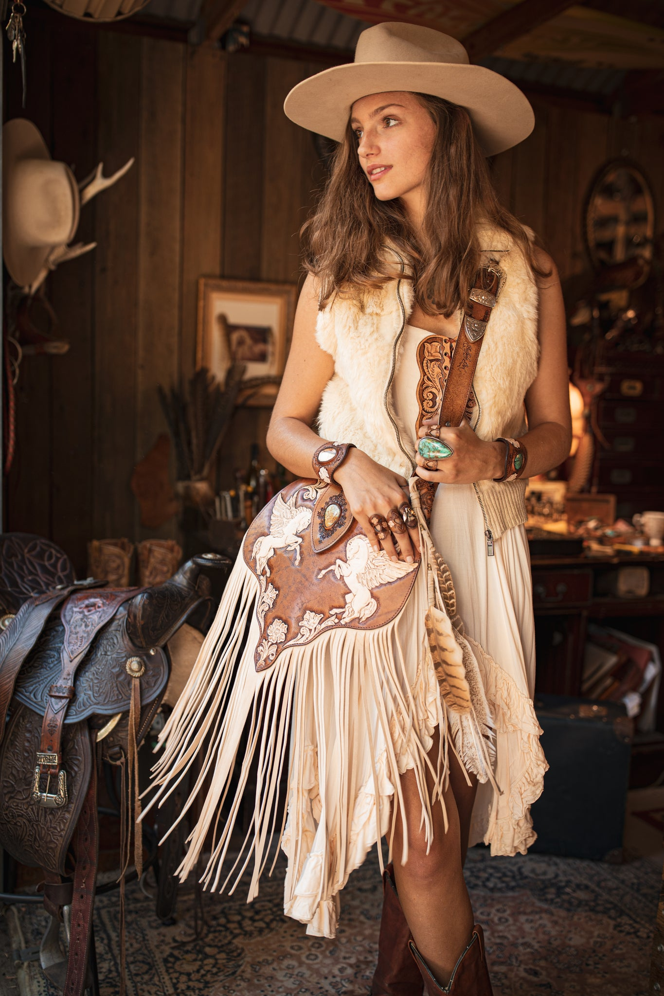 Cowgirl wearing handmade leather bag with painted pegasus and white tassels