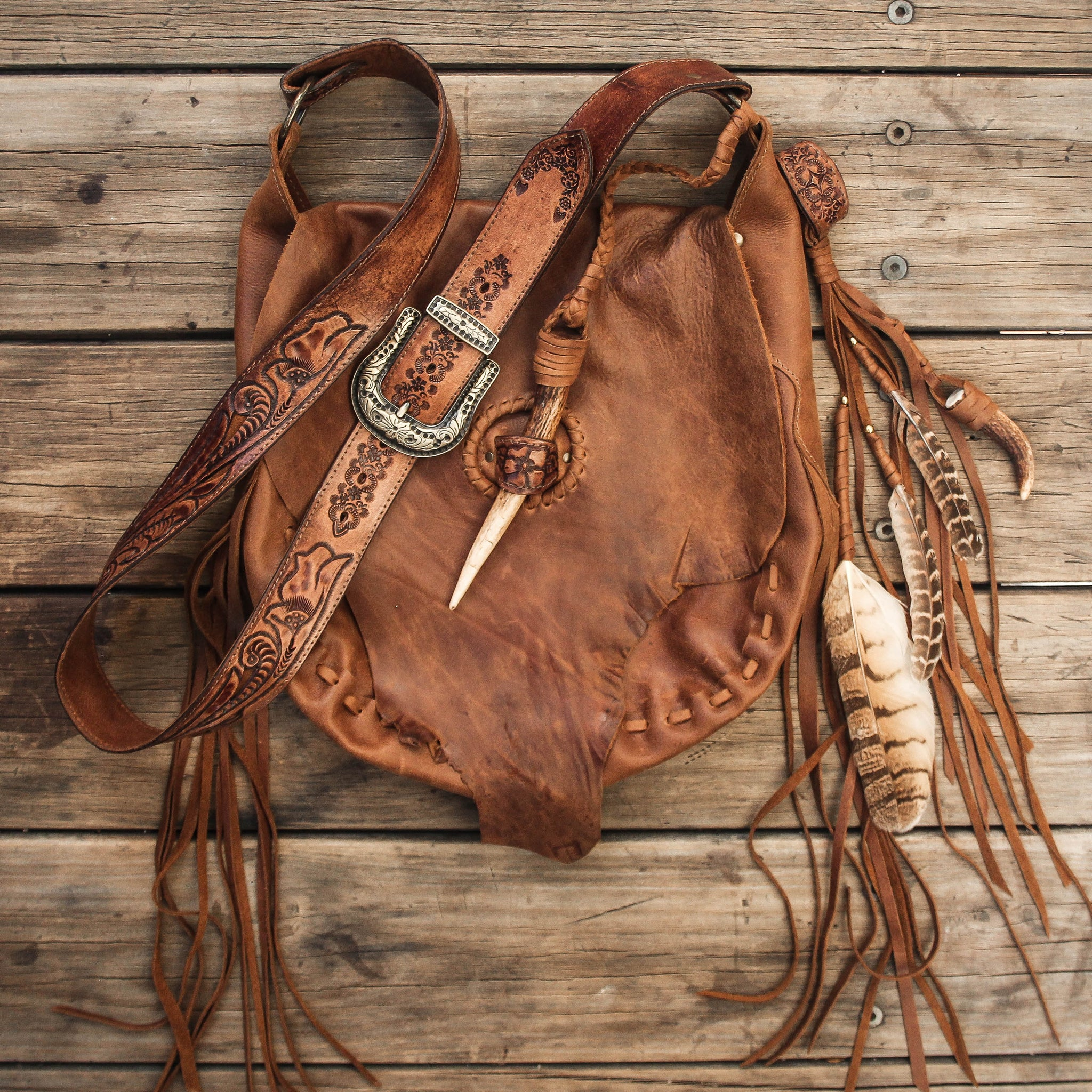 Raw Hyde Nomad Bag with Stag Horn Fastening in distressed tan leather.