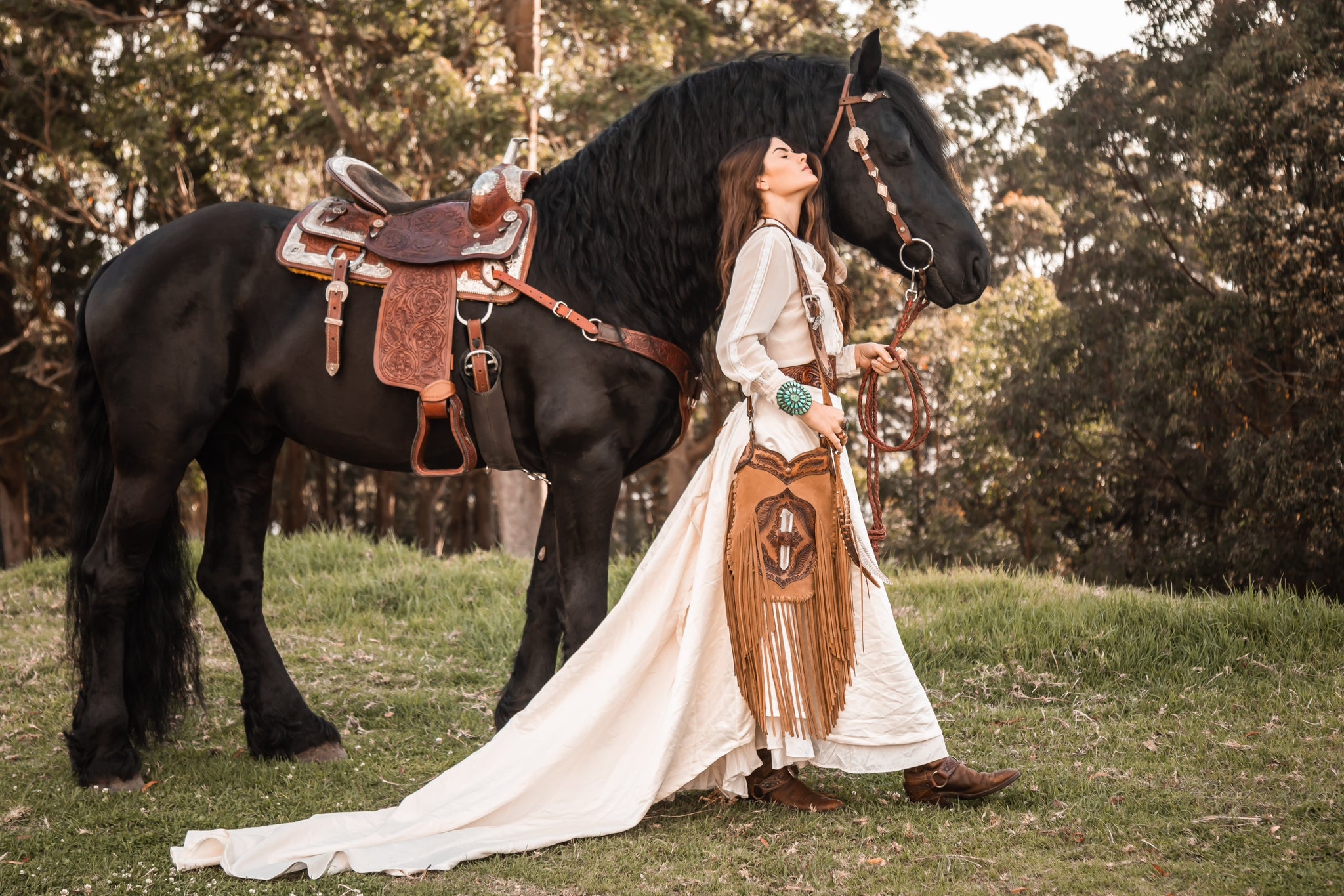 Black friesian horse with girl in a long white gown