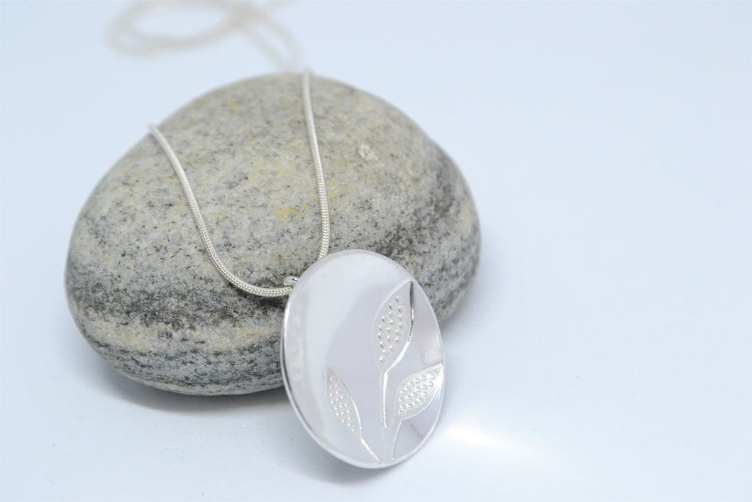 Round silver pendant with printed leaves on snake chain