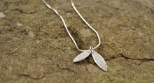 Silver double leaf pendant on chain.
