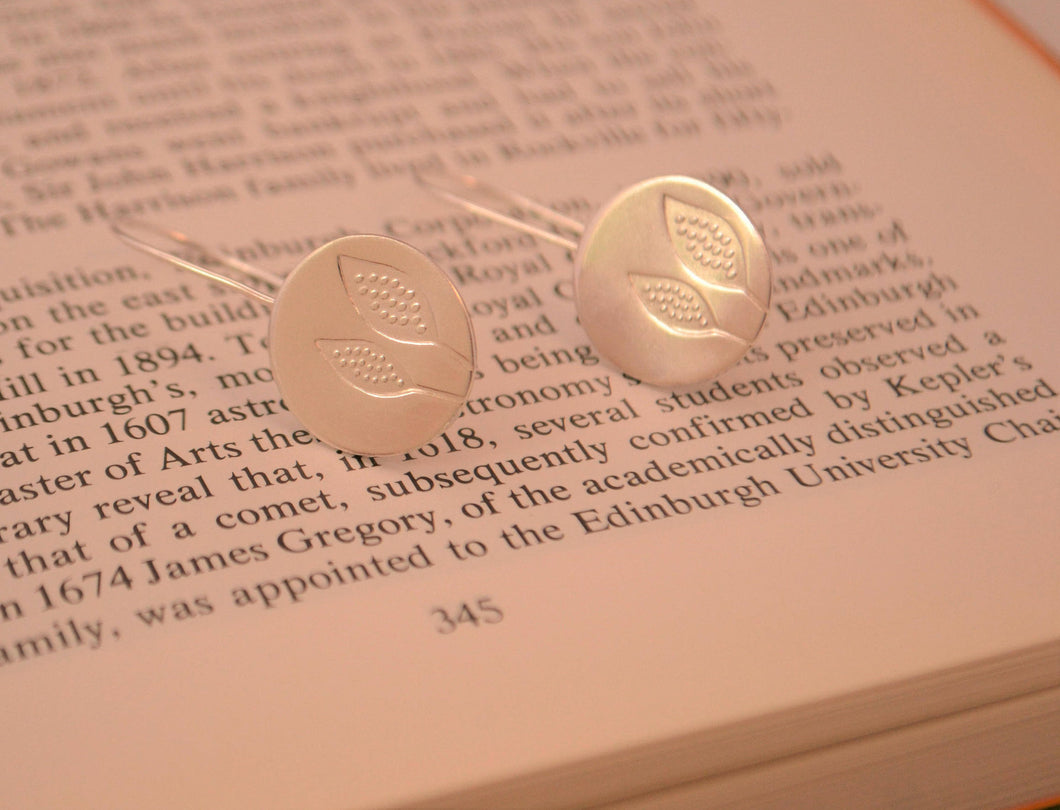 Round silver earrings with printed leaves