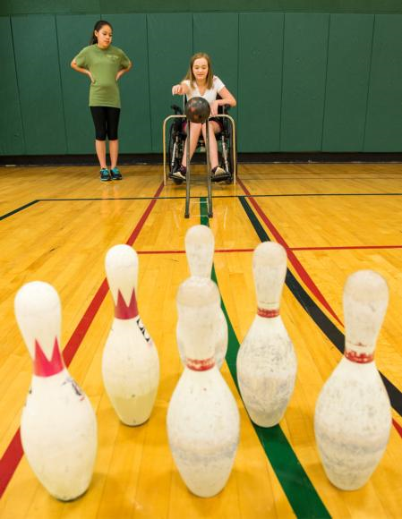 This student is learning the prerequisite skills for bowling in the community.