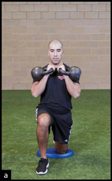 Figure 8.14 Half-kneeling alternating kettlebell press.