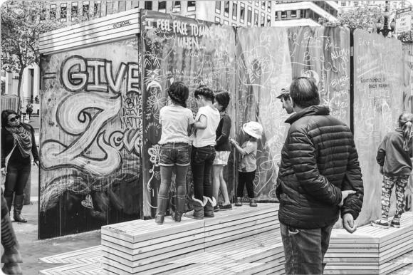 Children and adults interact with a pop-up chalk wall, which is a temporary interactive creative space for sharing ideas and artwork that was created by Youth Art Exchange members to inspire conversation with and creation by passersby and neighbors on a street corner in San Francisco.