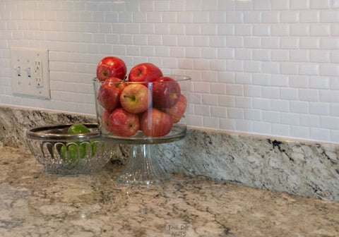 white kitchen backsplash with glass container of apples