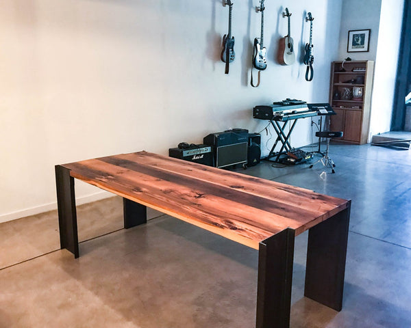 Handmade American reclaimed pine dining table with steel legs. Modern, industrial, sleek, minimalist design. Wood and metal dining room table in house.