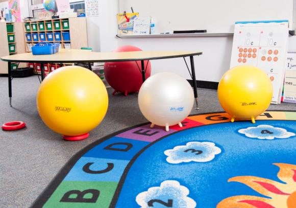 Classroom chairs can be removed and stability balls can be used as chairs instead. This simple change of furniture can help students engage core muscles while they do seat work.