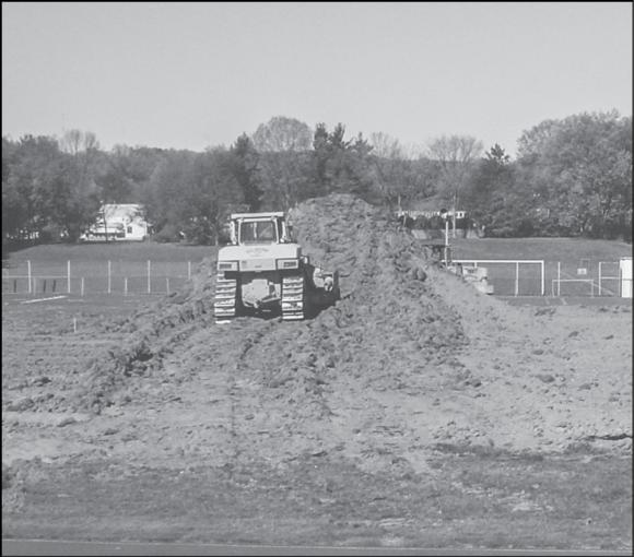 The first step in the process of converting a grass field to an artificial turf field is to remove the grass.