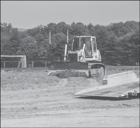 Once the grass is removed and enough topsoil is removed for drainage preparation, a laser-guided bulldozer will level the field.