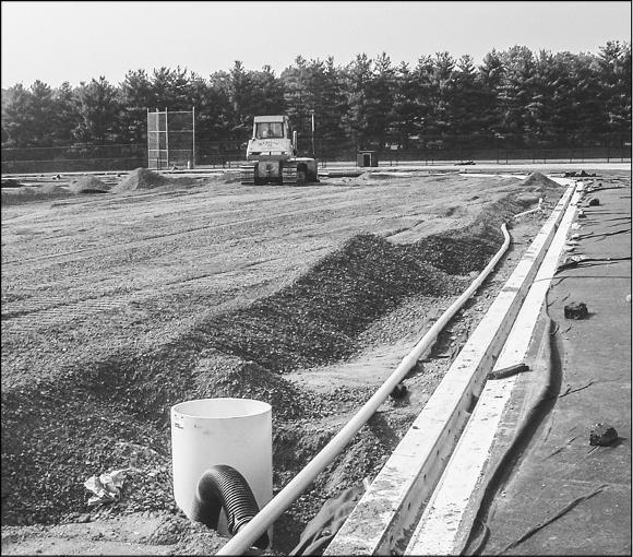 Once the field is leveled, a covering is placed over the soil to prevent weeds from coming through. Then, drainage pipes and stones large enough to allow for percolation are added before the final field surface is installed.