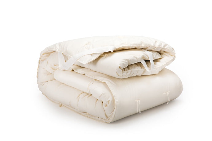 Wool mattress topper or mattress pad folded on white background