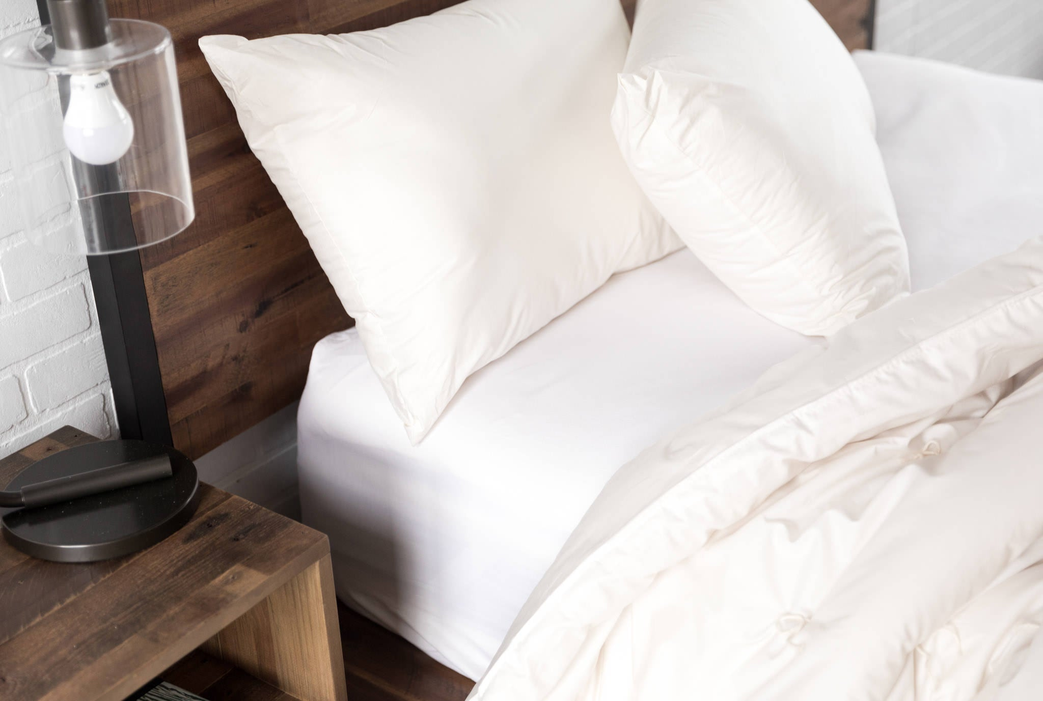Wool bedding, comforter, pillows, on wood bed with nightstand
