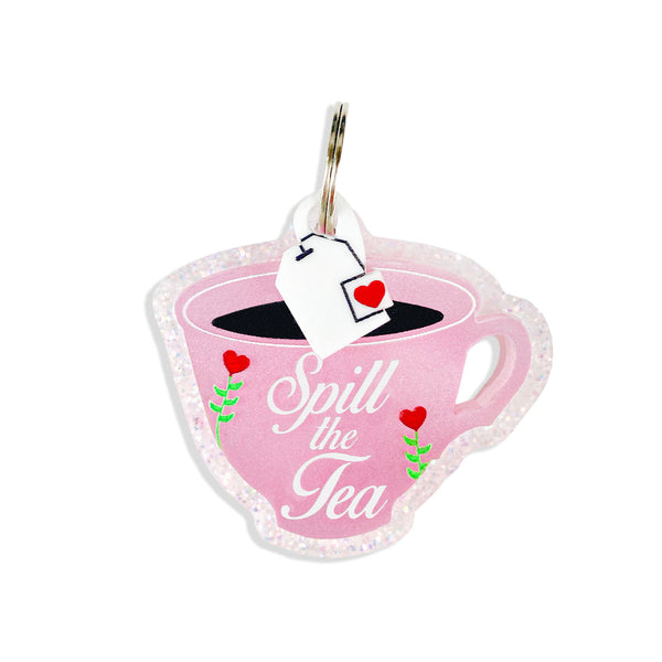 Pink tea cup dog tag with, spill the tea on the front, comes with a mini tea bag charm.
