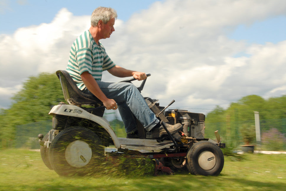 man mowing lawn on sit down lawn mower