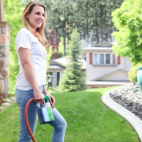 Lady standing in front yard with hose hooked up to Simple Lawn Solutions product