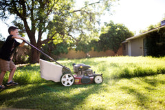 Boy mowing grass lawn