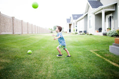 Boy playing with a ball in his yard