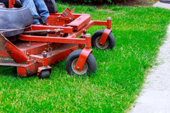 Closeup of red riding lawn mower cutting grass