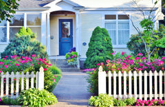 Home with picket fence garden and green lawn
