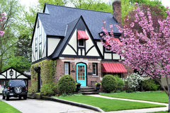 House with green spring lawn and flowering trees