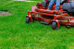 Large red riding mower cutting grass in a yard