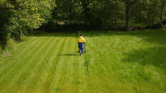 Man mowing large lawn with a push mower