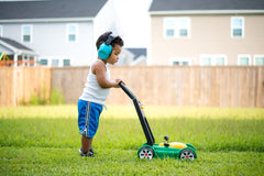 Toddler mowing the lawn with a play mower