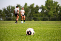 Two women standing on a soccer field with green grass