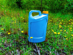 Blue Plastic canister of fertizilier on the grass with dandelions shown