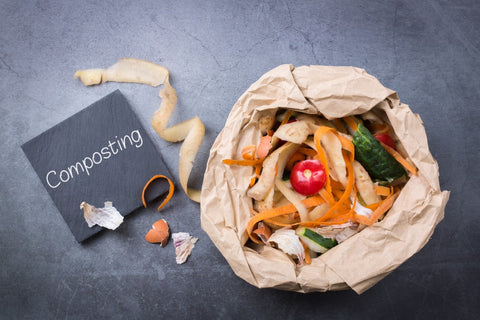"""""""Composting"""" written on chalkboard next to bag full of food scraps and leaves"""