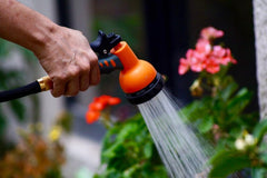 Someone holding a garden hose and watering their plants.