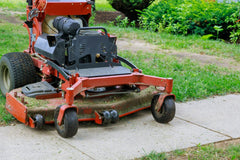 Red standing mower mowing lawn