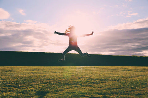 Person Jumping in the Sun on Green Grass