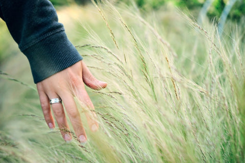 Woman running her hand in the grass.
