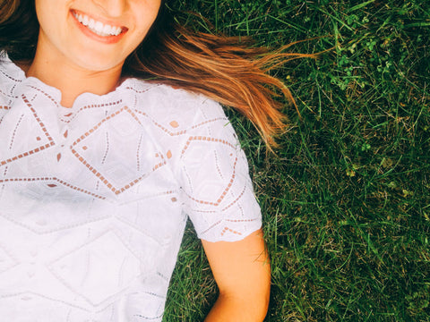 Woman laying in green grass.