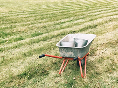 red and silver wheelbarrow holding silver buckets on cut lawn