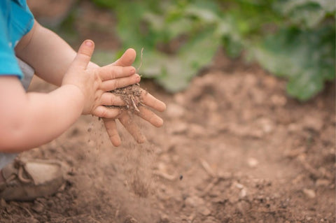 Baby hands wiping dirt off back onto ground