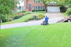 Man mowing his lawn on ride-on mower wearing blue shirt