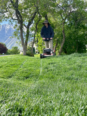 Adult with hat on mowing lawn