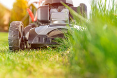 up close image from ground of big ride on lawn mower cutting grass