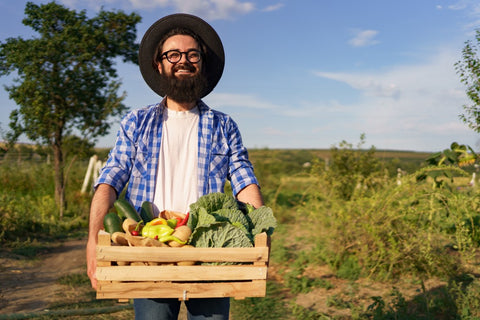 Man holding wood crate of full of vegetables in front of garden
